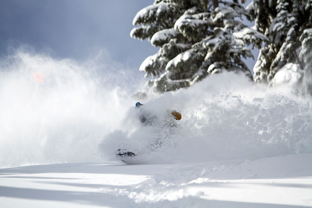snowboarder slashing through powder at China Peak