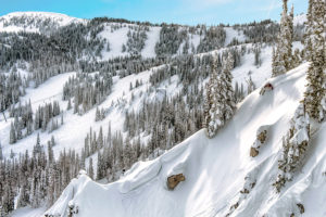 Skier riding cliffside at Mission Ridge