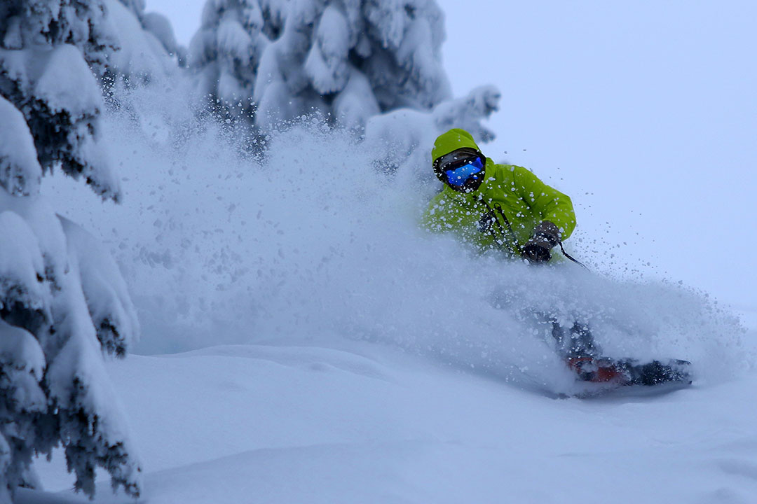 snowboarder slashing through powder